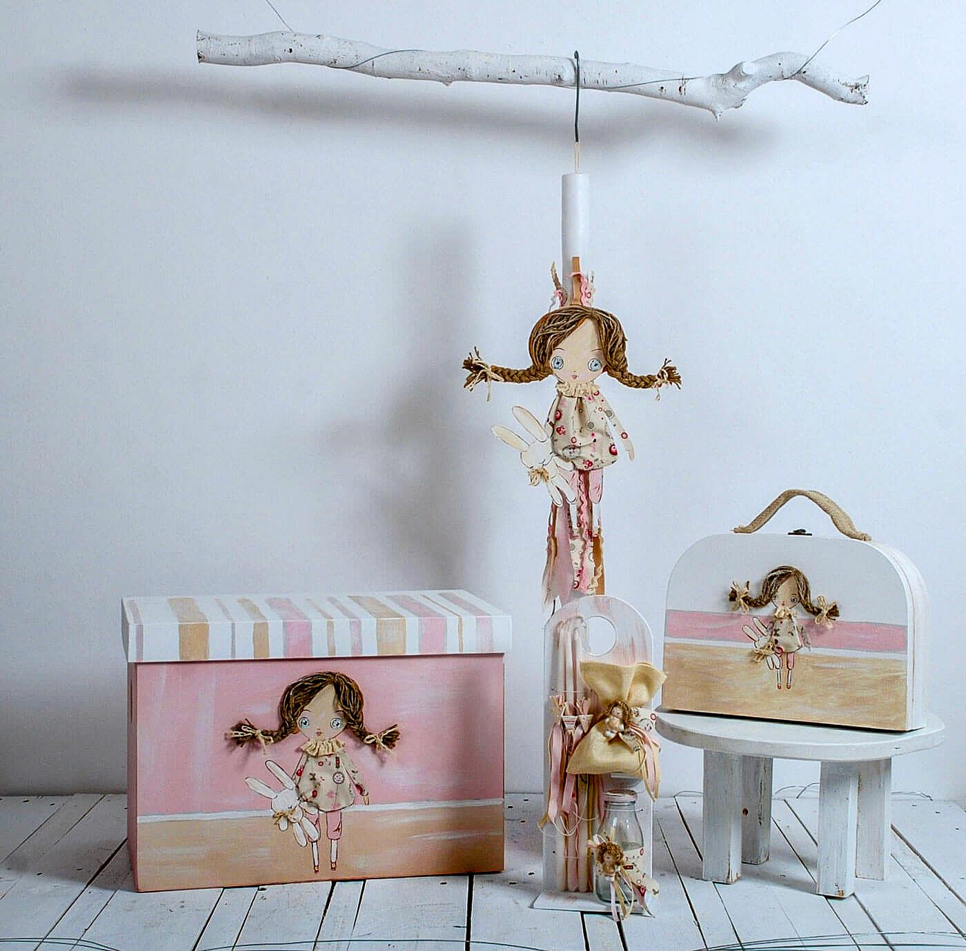 Βαπτιστικό κουτί με φορετό καπάκι σε παστέλ τόνους του ροζ και του μπεζ διακοσμημένο με πάνινη κούκλα. Το σετ συμπληρώνει αρμονικά η λευκή βαπτιστική λαμπάδα, το λαδοσέτ και το μίνι βαλιτσάκι. Η πάνινη κούκλα είναι το βασικό στοιχείο διακόσμησης σε αυτό το βαπτιστικό σετ για κορίτσια.