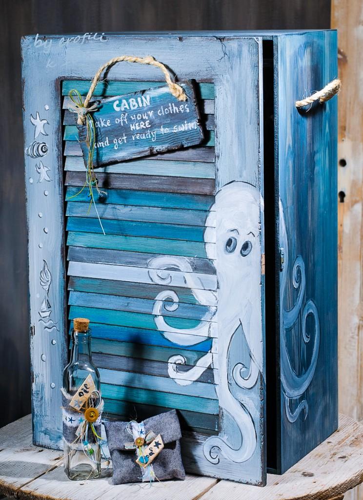 """Βαπτιστικό κουτί ντουλάπα για αγόρι 108 by erofili.  Χειροποίητο κουτί βάπτισης ντουλάπα για αγόρι όλο ζωγραφιστό στο χέρι σε χρώμα γαλάζιο και γκρι με θέμα θαλασσινό """"χταπόδι"""" και θήκες εσωτερικά για το ρούχο και τα αξεσουάρ της βάπτισης. Συνδυάζεται με την αντίστοιχη λαμπάδα καθώς και το λαδοσετ. Στο κατάστημα μας θα βρείτε μεγάλη συλλογή από βαφτιστικά υψηλής ποιότητας και αισθητικής, λαδοσετ, μαρτυρικά, ευχολόγια, λαμπάδες μπομπονιέρες και ότι άλλο μπορεί να χρειαστείτε για την βάφτιση."""