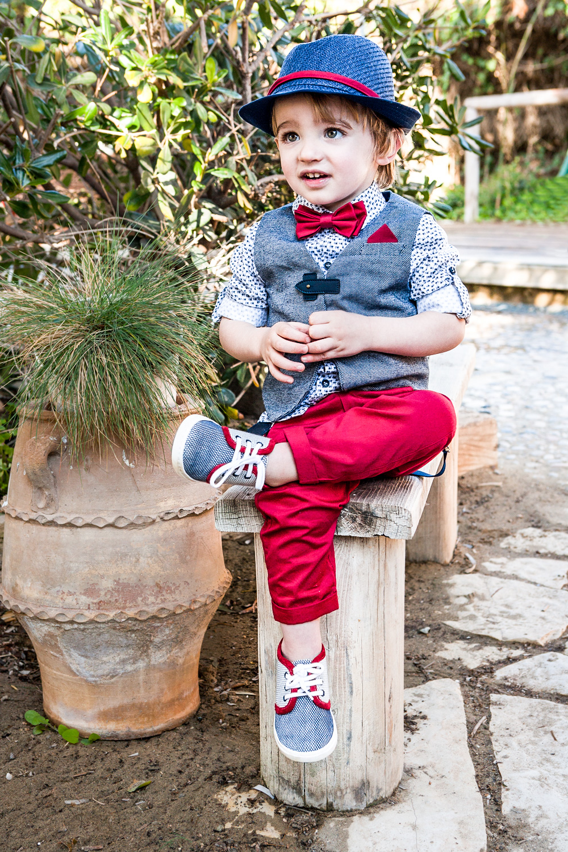 Bambolino βαφτιστικό σετ για αγοράκι που αποτελείται από παντελόνι σε κόκκινο χρώμα με βαμβακερό πουκάμισο και γκρι γιλέκο. Το σετ συνδυάζεται με παπιγιόν στο χρώμα του παντελονιού, με τιράντες κα ψαθάκι μπλε για το κεφάλι.