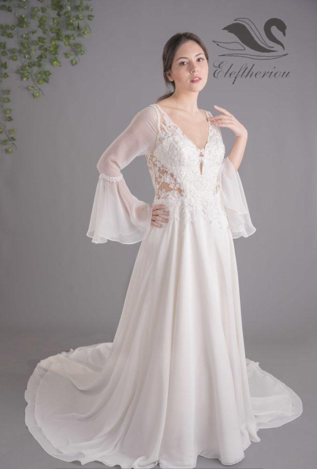 Νυφικό διακοσμημένο με δαντέλα στο μπούστο και διαφάνεια στην πλάτη με φούστα και μανίκια από μουσελίνα.